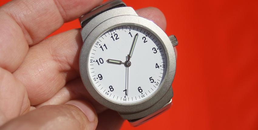 часы в руке на красном фоне